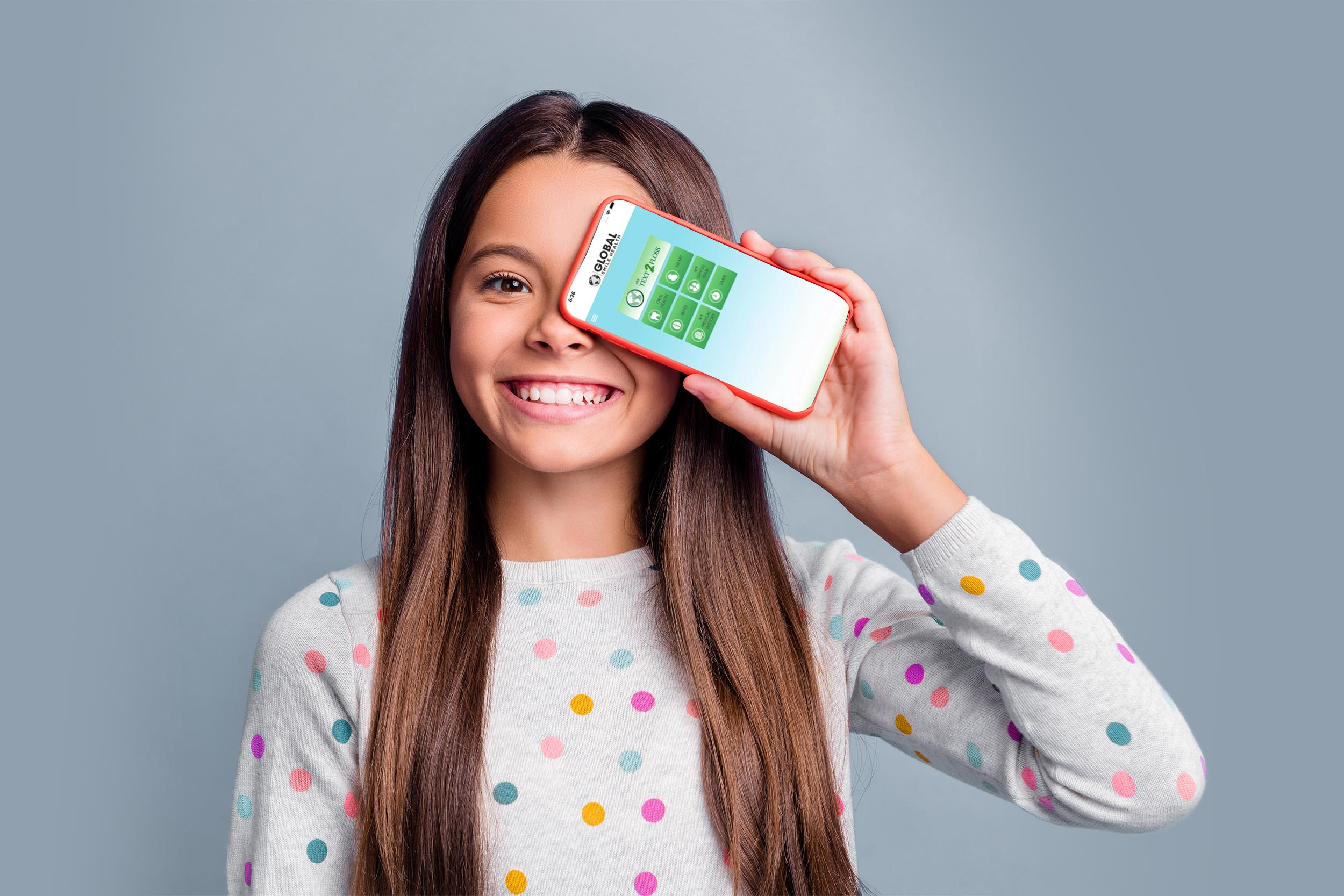 Photo portrait of happy girl covering one eye with phone with blank space isolated on bright purple colored background.
